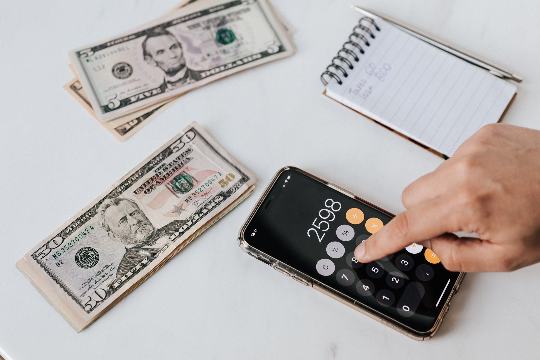 crop unrecognizable financier using calculator on smartphone near dollar banknotes